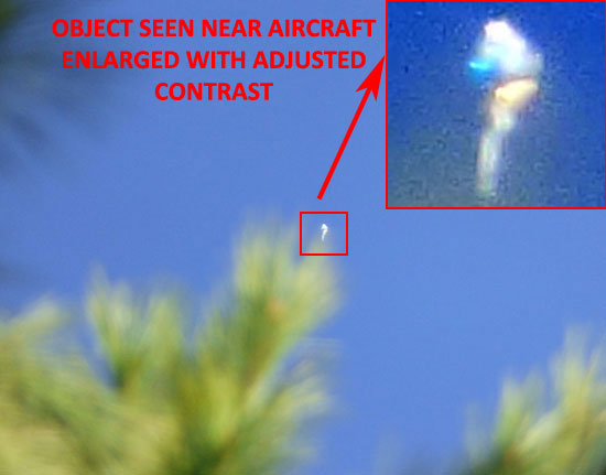 PHOTO & ENLARGEMENT OF STRANGE CRAFT NEAR COMMERCIAL JET.