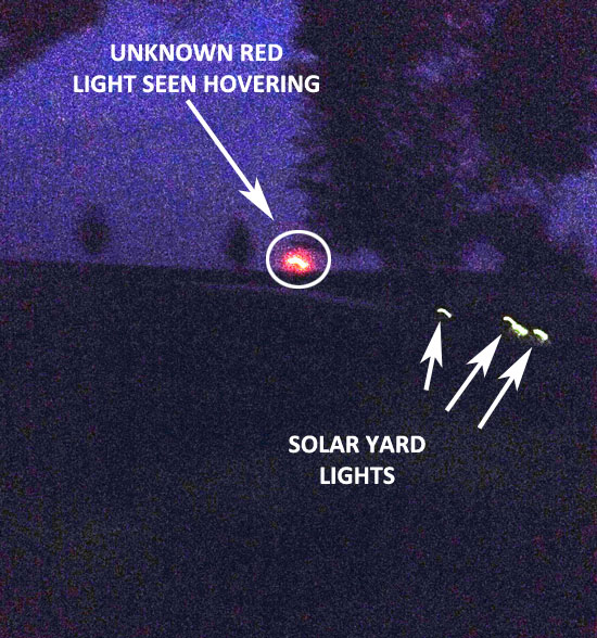 UNKNOWN RED LIGHT SEEN HOVERING OVER FIELD.