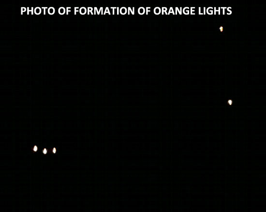 CELL-PHONE PHOTO TAKEN OF ORANGE LIGHTS.