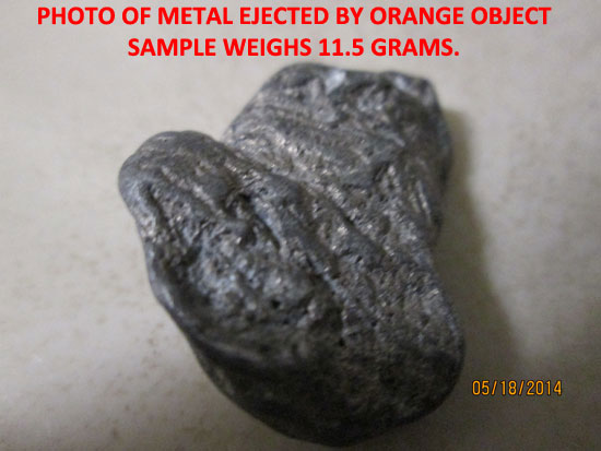PHOTO OF 1 PIECE OF METALLIC DEBRIS EJECTED BY ORANGE OBJECT.
