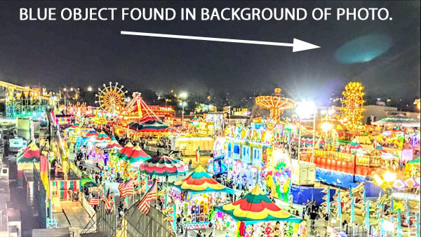 BLUE OBJECT FOUND IN BACKGROUND OF PHOTO OF FAIR.