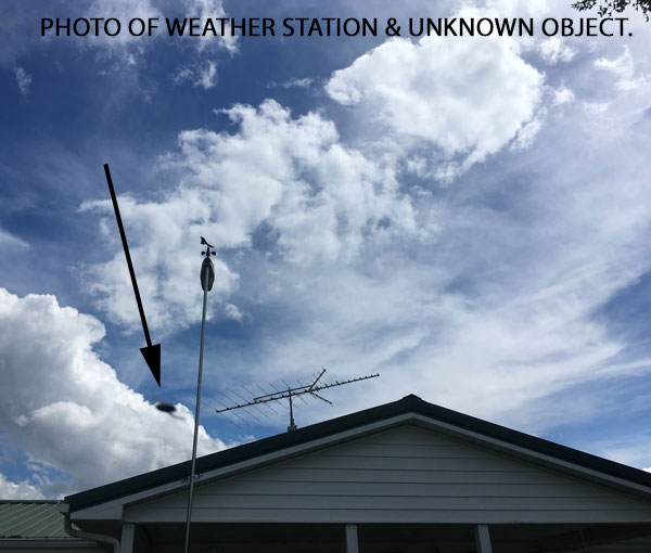 PHOTO OF WEATHER STATION & UNKNOWN OBJECT FOUND IN BACKGROUND.