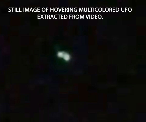 STILL IMAGE OF HOVERING MULTICOLORED UFO EXTRACTED FROM VIDEO.