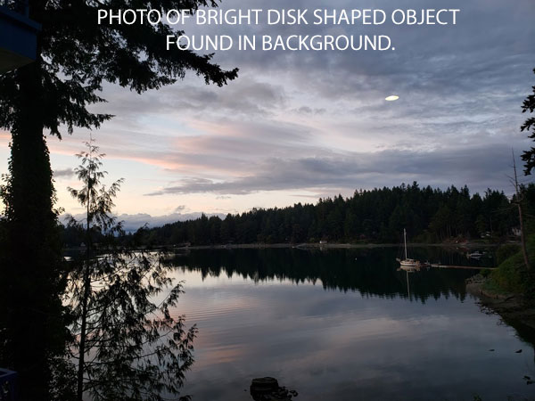 PHOTO OF BRIGHT DISK SHAPED OBJECT FOUND IN BACKGROUND.