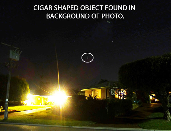 CIGAR SHAPED OBJECT FOUND IN BACKGROUND OF PHOTO.