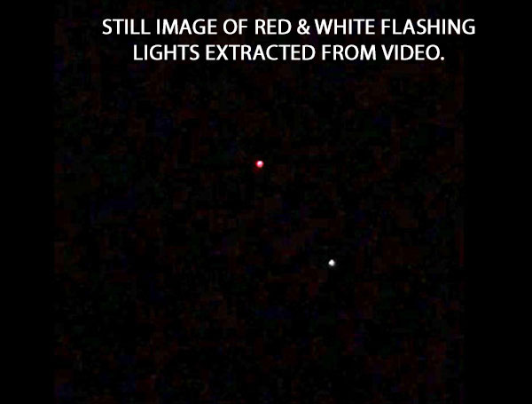 STILL IMAGE OF RED & WHITE FLASHING LIGHTS EXTRACTED FROM VIDEO.