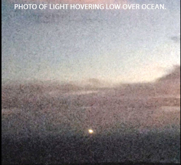 PHOTO OF YELLOW-WHITE LIGHT SEEN HOVERING OVER OCEAN.