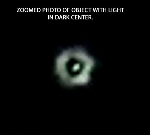 ZOOMED PHOTO OF OBJECT WITH LIGHT IN DARK CENTER.