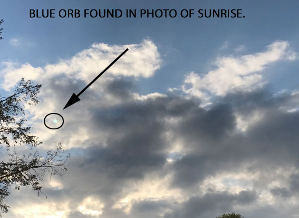 BLUE ORB FOUND IN BACKGROUND OF PHOTO OF SUNRISE.