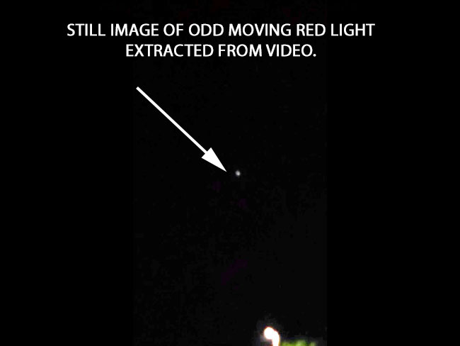 STILL IMAGE OF ODD MOVING RED LIGHT EXTRACTED FROM VIDEO.